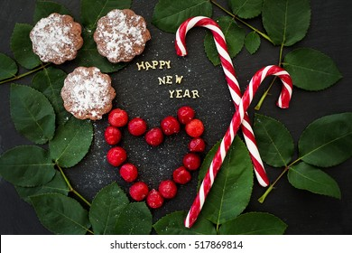 inscription of new year on a black board with cupcakes and candy red - Shutterstock ID 517869814
