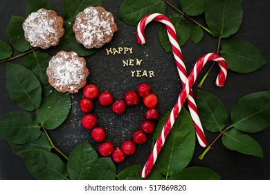 inscription of new year on a black board with cupcakes and candy red - Shutterstock ID 517869820
