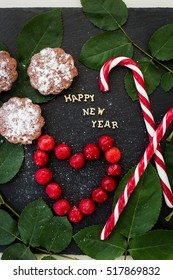 inscription of new year on a black board with cupcakes and candy red - Shutterstock ID 517869832