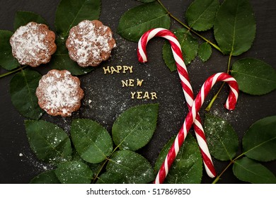 inscription of new year on a black board with cupcakes and candy red - Shutterstock ID 517869850