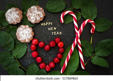 inscription of new year on a black board with cupcakes and candy red - Shutterstock ID 517869865