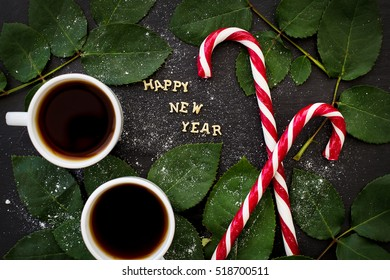 inscription of new year on a black board with sprigs of leaves and red candy - Shutterstock ID 518700511