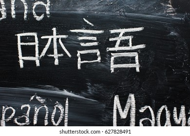 """Inscription on a black chalk board: word """"japanese"""" written in japanese language cropped with parts of words in differents languages"""