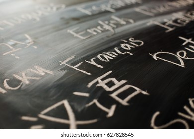 "Inscription on a black chalk board written ""french"" in french among others names of languages wrote on these languages: chinese, serbian, german, hebrew, english"