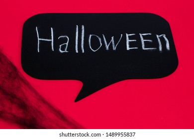 """The inscription on the board """"Halloween"""" on a red background and a black web. Halloween decoration"""