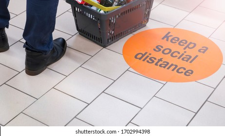 the inscription on the floor of the supermarket: keep a social distance. Selective focus