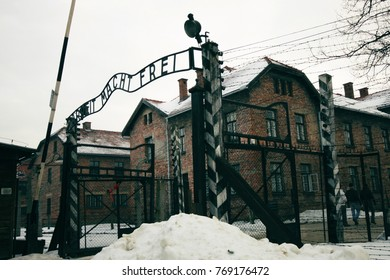 "The inscription on the gate to the Auschwitz concentration camp (Poland): ""Work makes you free"". Barracks and barbed wire in a concentration camp in Auschwitz."