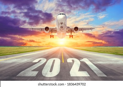 The inscription on the runway 2021 surface of the airport runway with take off airplane. Concept of travel in the new year, holidays