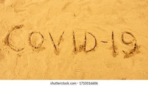 Inscription on the sand covid-19