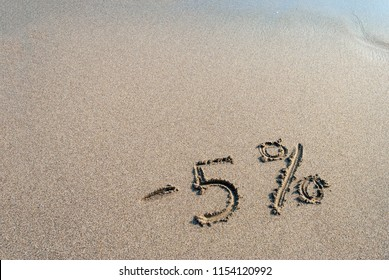 inscription on the sand minus 5 percent,  - 5 %