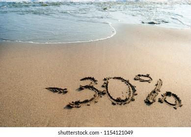 inscription on the sand minus thirty percent, - 30 %, sea wave on the sand with the inscription thirty