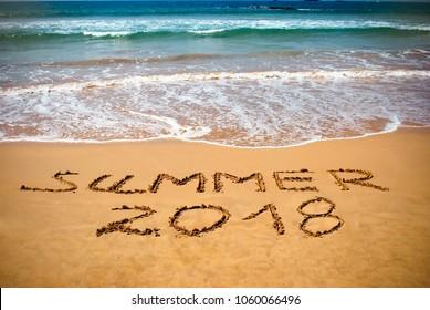Inscription on wet sand Summer 2018. Concept photo of summer vacation on the tropical island ocean beach.