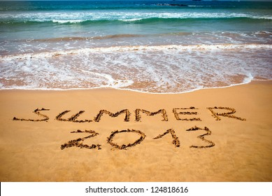 Inscription on wet sand Summer 2013. Concept photo of summer vacation.