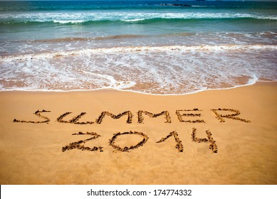Inscription on wet sand Summer 2014. Concept photo of summer vacation.