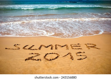 Inscription on wet sand Summer 2015. Concept photo of summer vacation.