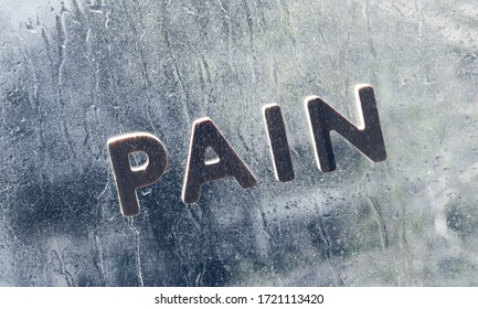 Inscription pain on wet glass in the rain. Outside rain, on the soul of pain. symbol of depression, sadness concept