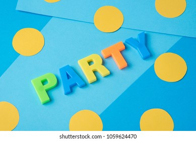 The inscription of the party with plastic letters on a blue paper background with yellow circles