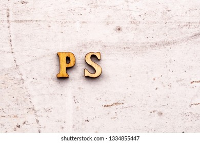 Inscription PS post scriptum abbreviation in wooden letters on a light background