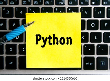 "The inscription ""PYTHON"" language on a yellow sheet of sticker paper on the background of a computer keyboard."