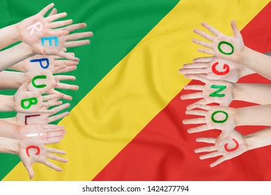 Inscription Republic of the Congo on the children's hands against the background of a waving flag of the Republic of the Congo