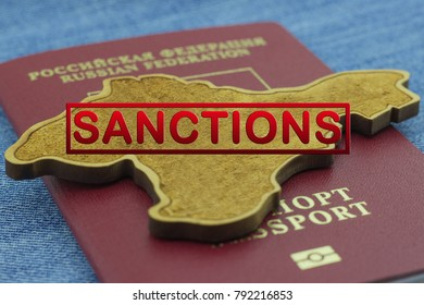 Inscription Sanctions. wooden map of Crimea lies on the red passport of Russia on a blue background