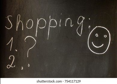 Inscription Shopping chalk on a black board with a question mark and a picture of a smiling face. Preparing for shopping, shopping list, good mood.