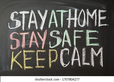 Inscription stay at home stay safe keep calm. Outbreak Warning. written white chalk on blackboard in connection with epidemic of coronavirus worldwide. Covid 19 pandemic Text on black background