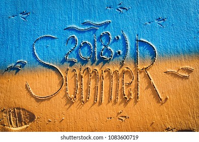 The inscription summer 2018 is written on the colourfull sand. The inscription is made by hand. Blue and yellow postcard.