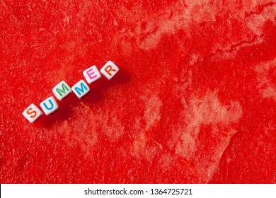 The inscription of the summer is made of cubes with letters lying on a watermelon