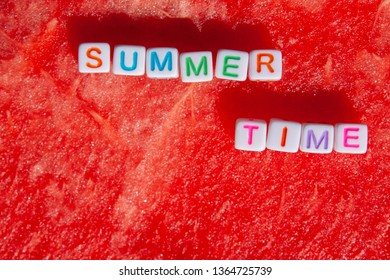 The inscription of the summer time is made of cubes with letters lying on a watermelon with space for text