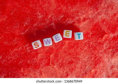 The inscription of the sweet is made of cubes with letters lying on a watermelon
