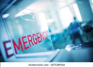 """Aufschrift """"Dringlichkeit"""" auf dem Plastikglas vor dem Hintergrund der Krankenhausnotaufnahme."""