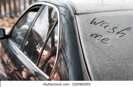 Inscription wash me on the dirty car window