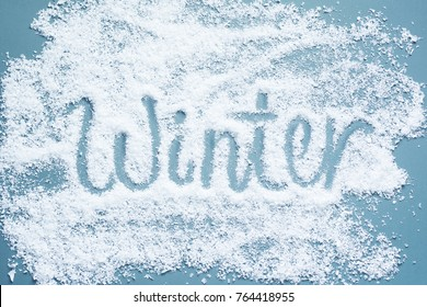 Inscription WINTER is handwritten by a close up on artificial snow on a blue background.