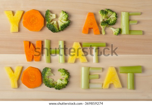inscription you are what you eat on wooden background, text from farm products, letters from vegetables, carrots, celery, potatoes, broccoli, closeup, chopped vegetables, macro