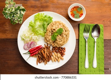 Insect food - Bamboo worm fried insect on the plate with old wooden table background. Insect food is the healthy meal high protein diet concept and popular snack food in Thailand, Top view