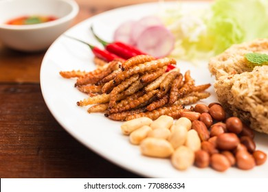 Insect food - Bamboo worm fried insect on the plate with old wooden table background. Insect food is the healthy meal high protein diet concept and popular snack food in Thailand