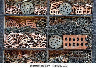 insect hotel for nesting wild insects which needs irregular chambers which in the city there is a lack of pieces of brick perforated wood reeds and sticks stacked in a box covered with mesh