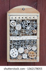 Insect hotel on a red wall made of reed and drilled holes in wood of different diameter to suit all kind of insects
