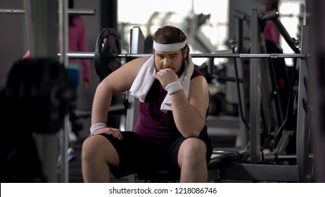 Insecure chubby man in gym feeling upset because of excess weight, shyness
