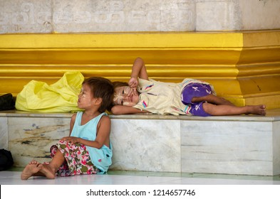 Insein, Yangon / Myanmar - March 20, 2012: Two homeless sisters resting at Kyak Daw Kyi Pagoda