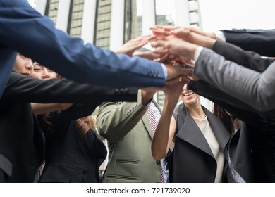 Inselective focus of close up side view of young business people putting their hands together. Businessman friends with stack of hands showing unity and teamwork.