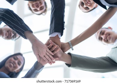 Inselective focus of close up young business people putting their hands together. Businessman friends with stack of hands showing unity and teamwork.Low angle and looking to camera.