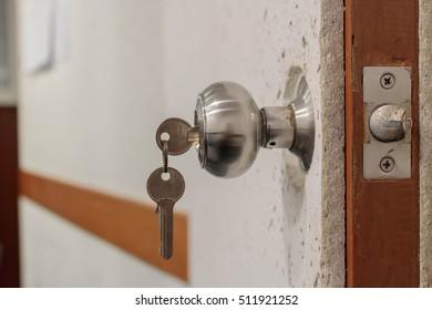 Insert key into lock of the door soundproofing. (beside)