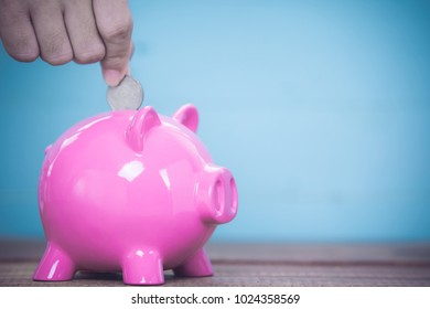 Inserting a coin into a pink piggy bank .
