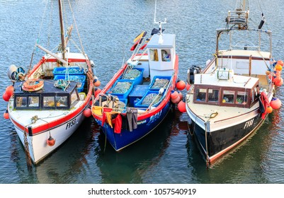 Inshore fishing boats or trawlers moored in Mevagissey harbour in Cornwall. Mevagissey, UK - 27th March 2018