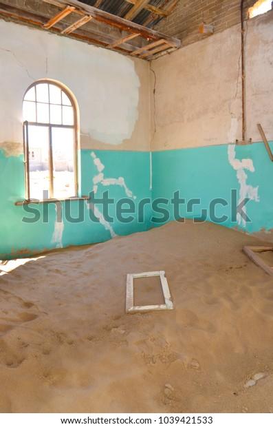 Inside an abandoned house reclaimed by sand. Kolmanskop ghost town, Namib desert, Namibia