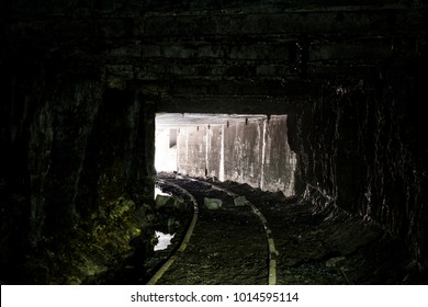 Inside the abandoned Mathies coal mine in western Pennsylvania. Closed in 1992, two mine car tracks enter into a darkened cavern.