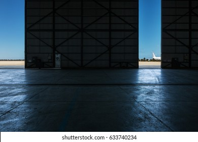 Inside an airport hanger looking out to the runway