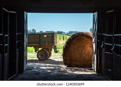 Inside a barn looking outside, with a hay roll or bale and a truck trailer with a blue sky and green grass